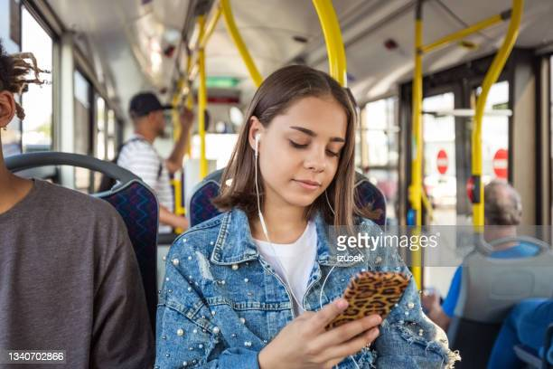 girl using smart phone in public transport - izusek stock pictures, royalty-free photos & images