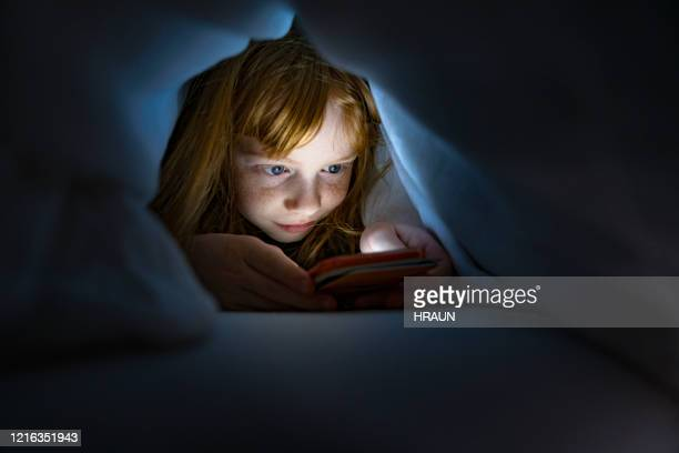 girl using smartphone in dark, close up, low angle. - solo una bambina femmina foto e immagini stock