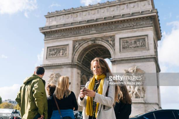 Girl using smartphone in front of the Arc de Triomphe