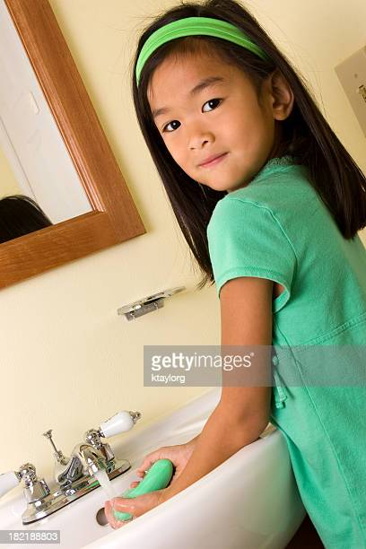 Girl using soap to wash hands