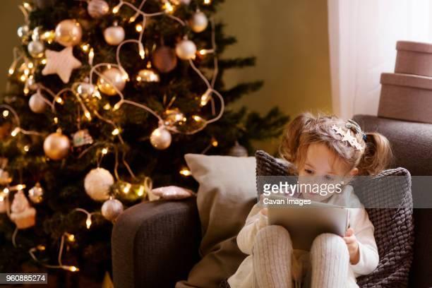 Girl using tablet computer while sitting on sofa during Christmas