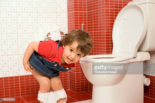 girl using toilet - little girls bent over stock photos and pictures