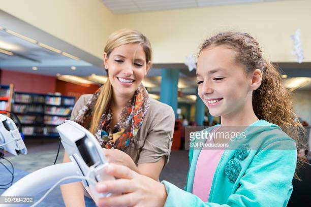 Girl using touch screen device to listen to library audiobook