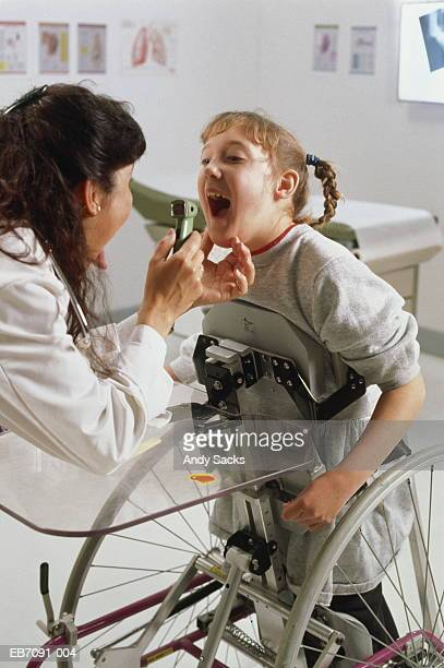 girl (9-11) using upright wheelchair,being examined by doctor - leaning disability stock pictures, royalty-free photos & images