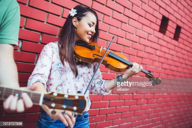 violinista de la chica en la calle - stringed instrument fotografías e imágenes de stock