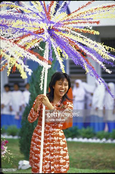Girl w big smile in native print dress holding umbrella of feathers adding local color to festivities surrounding Nancy Reagan's visit