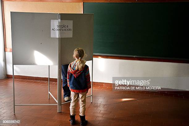 A girl waits for her mother to prepare her ballot to vote for the Portugal's presidential election at a polling station located at school in Oeiras...