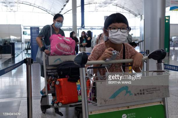 Girl waits in the check-in queue for her flight to Britain at Hong Kong's International Airport on July 18 the day before a deadline by the British...
