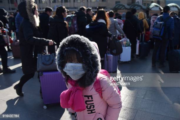 A girl waits outside a railway station in Beijing on February 10 as travellers depart the capital ahead of the Lunar New Year China is in the midst...