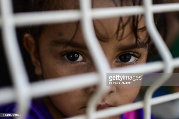 TOPSHOT A girl waits to be given asylum or a humanitary visa at the immigration office on the MexicoGuatemala international bridge in Ciudad Hidalgo...