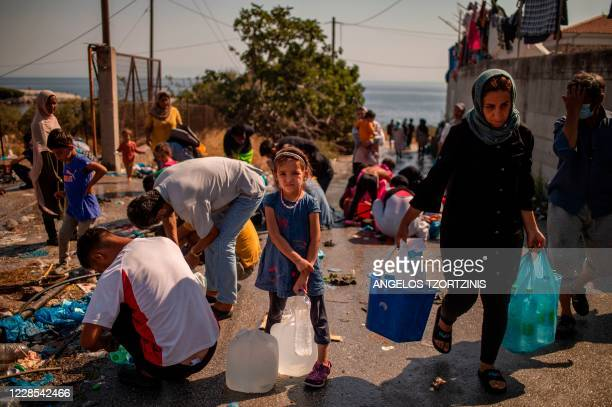Girl waits to fill bottles with water near a temporary migrant camp on the Greek Aegean island of Lesbos on September 16 after the Moria camp was...
