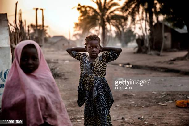 A girl waits to pump water from a well at Malkohi refugee camp in Jimeta Adamawa State Nigeria early on February 19 four days ahead of the country's...