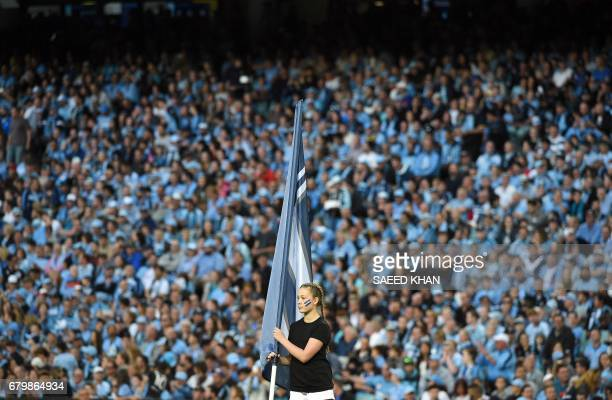 TOPSHOT A girl waits with the Melbourne victory flag for an opening ceremony of the 2017 ALeague Grand Final match between Sydney FC and the...