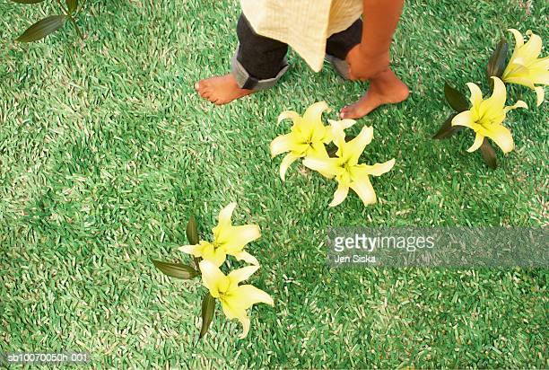 Girl (6-7 ) waking on grass with flower, low section, view from above