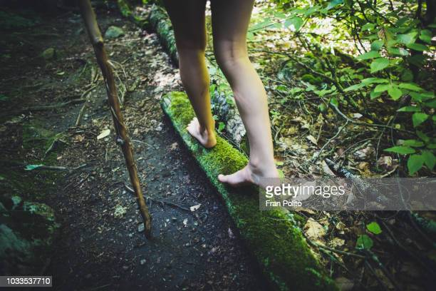 girl waling on a mossy log in the woods. - scalzo foto e immagini stock