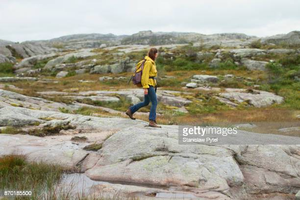 Girl walking alone in wild, rocky environment