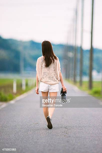 Girl walking along country road with camera