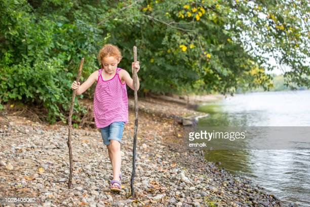 girl walking along riverbank with two large sticks - lake auburn stock photos and pictures