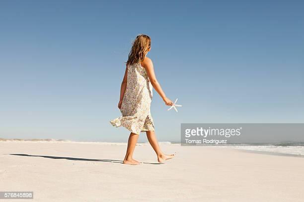 Girl (8-9) walking along sandy beach