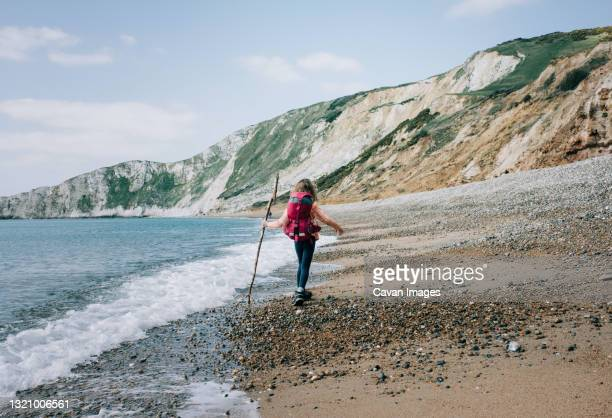 girl walking along the jurassic coast with a stick on a beautiful day - jurassic coast stock pictures, royalty-free photos & images