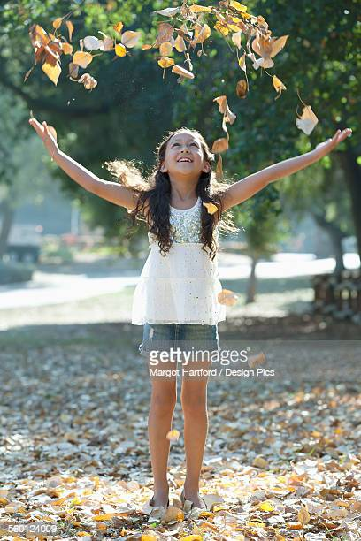 a girl walking and playing in autumn leaves - free up skirt pics stock photos and pictures