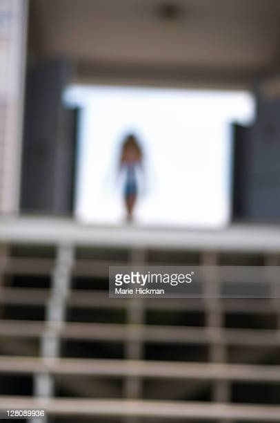 Girl walking at end of wooden stair