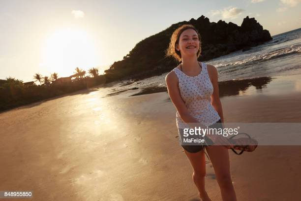 Girl walking at the beach in Fernando de Noronha by sunset