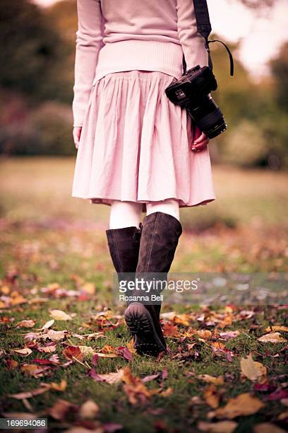 Girl walking away in autumn leaves with camera