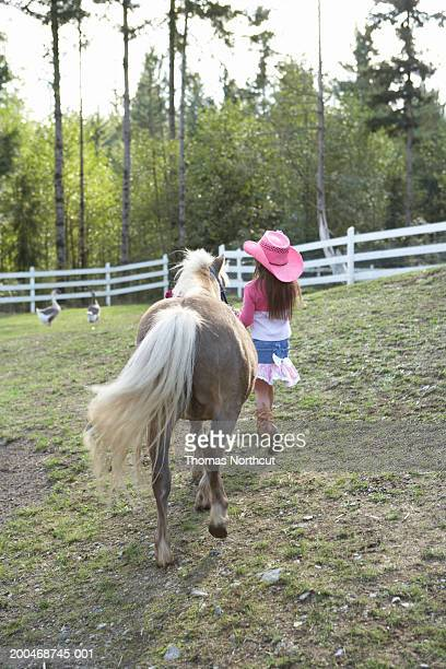 Girl (5-7) walking beside Shetland pony in pasture, rear view