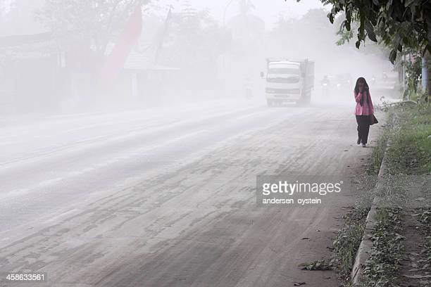 girl walking by a road covered in volcanic ash. - ash stock pictures, royalty-free photos & images