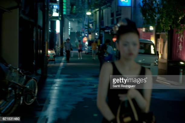 Girl walking by night in the neighborhood of Gion in kyoto