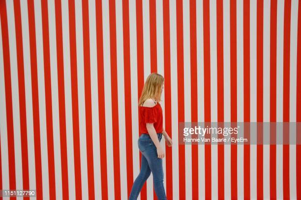 Girl Walking By Red Striped Wall