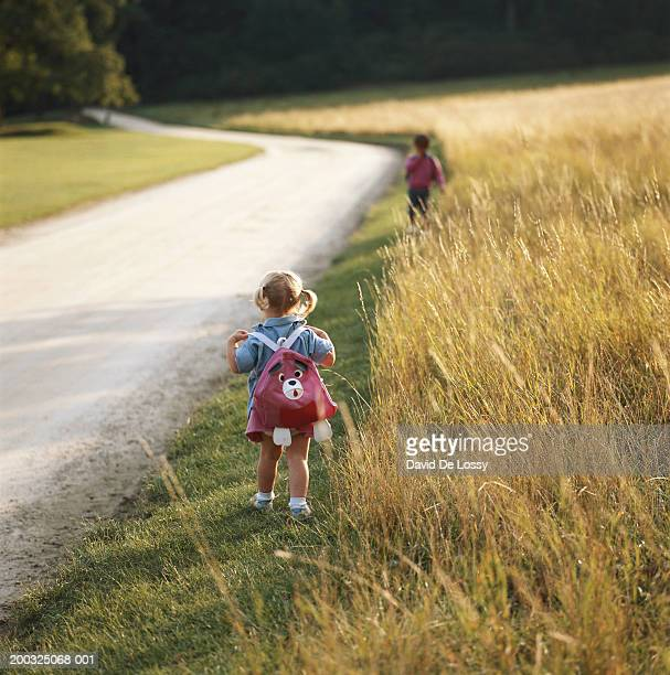 Girl (2-4) walking by road side with satchel