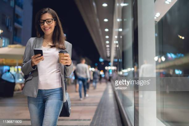 girl walking city streets with mobile and coffee - gray coat stock pictures, royalty-free photos & images