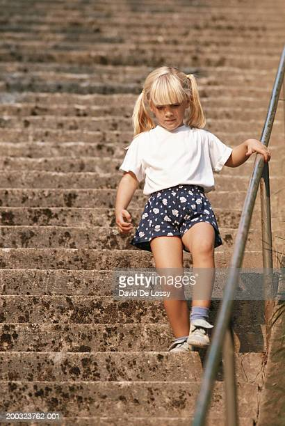 Girl (6-7) walking down staircase