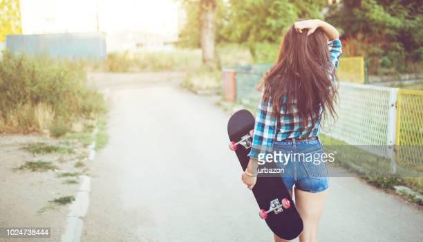 jeune fille marchant dans la rue avec planche à roulettes - fesse enfant photos et images de collection