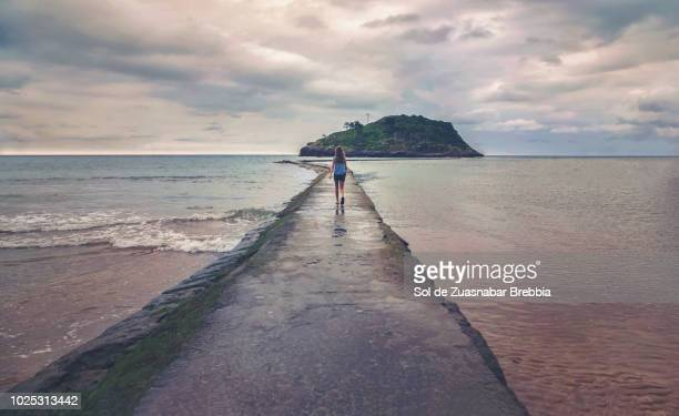 Girl walking forward to land on a path surrounded by sea