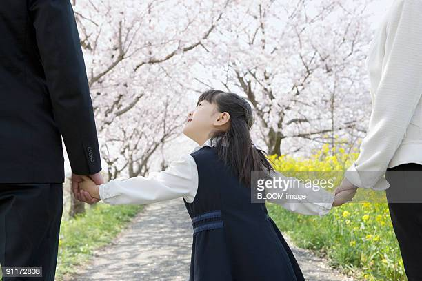 Girl walking hand in hand with parents