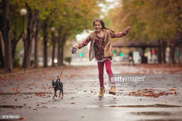 Girl walking her puppy in the park on a rainy day