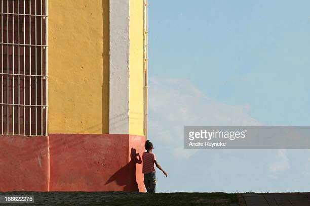 CONTENT] A girl walking home with her shadow captured in late afternoon sun captured as cape on the colourful arhitecture Trinidad Cuba