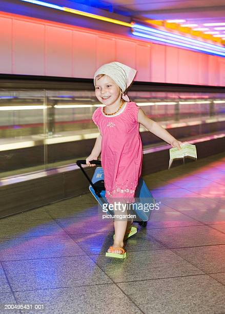 Girl (2-4) walking in airport, smiling