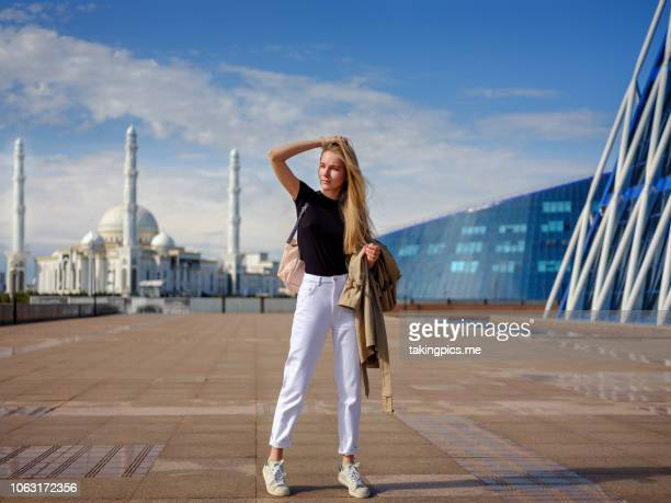 girl walking in center astana - white pants stock pictures, royalty-free photos & images