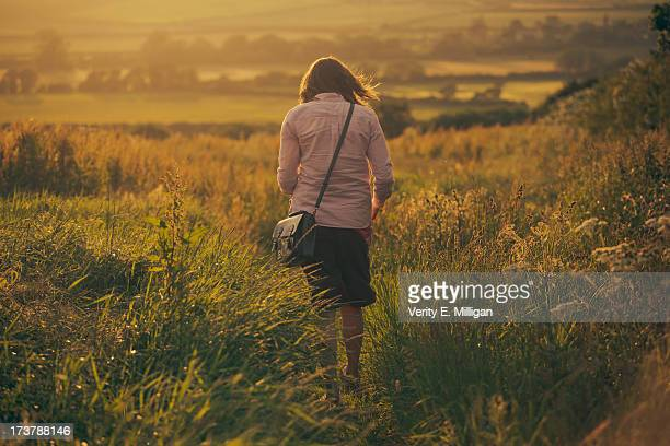Girl walking in field of crops at sunset