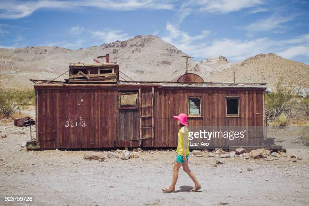 Girl walking in front of an abandoned  railroad wagon in the ghost town of Rhyolite, Nevada. She wears a pink hat and shorts.