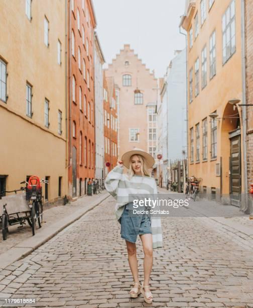 girl walking in oldest street in copenhagen, denmark - modewoche stock-fotos und bilder