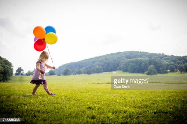 girl walking in rural field with bunch of colourful balloons - multi colored dress stock pictures, royalty-free photos & images