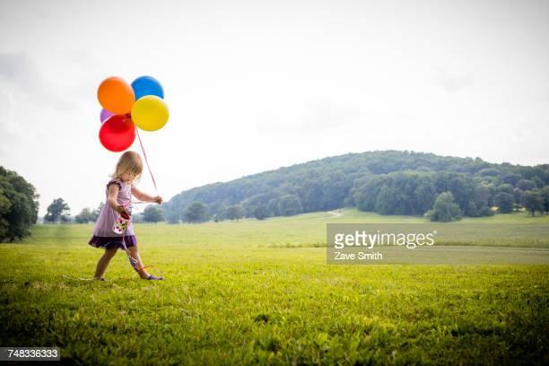 girl walking in rural field with bunch of colourful balloons - flerfärgad klänning bildbanksfoton och bilder