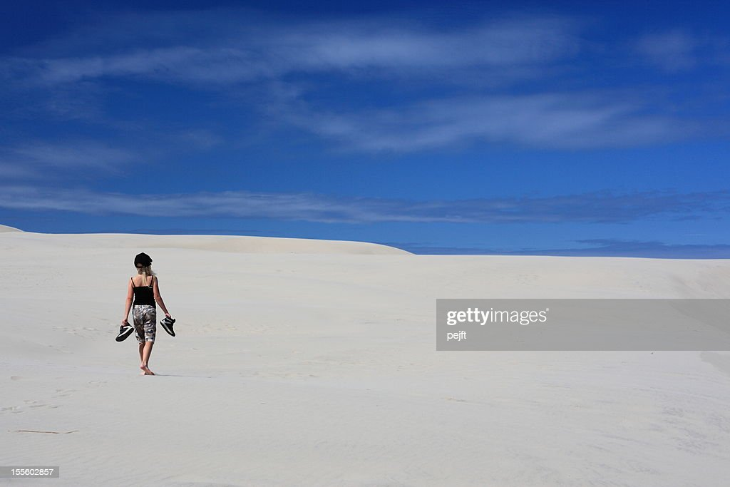 Girl walking in sand dunes / desert : Stock Photo