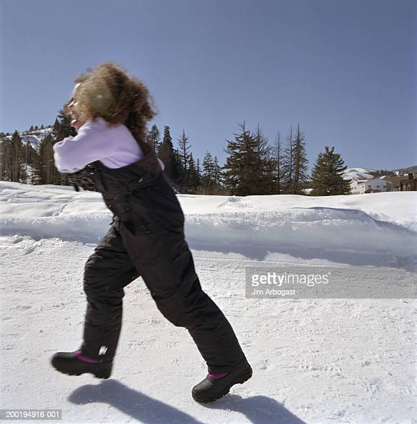 Girl (6-8) walking in snow field, side view