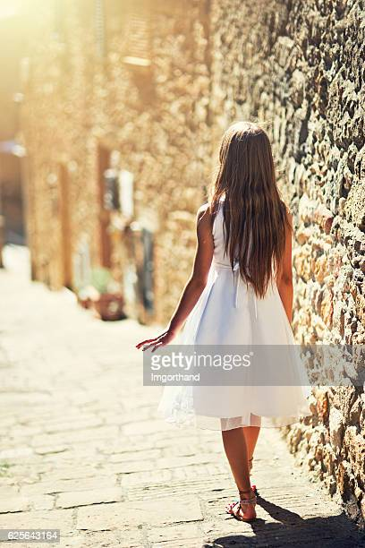 Girl walking in the sunny italian street